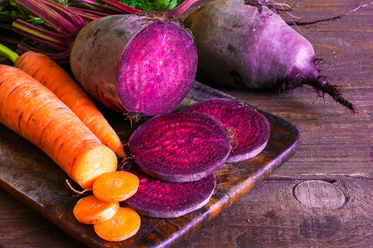 fresh beets and carrots on wooden background