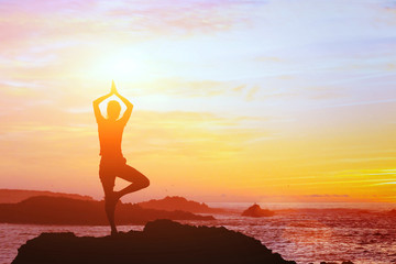 beautiful yoga background, silhouette of woman on the beach at sunset, mindfulness