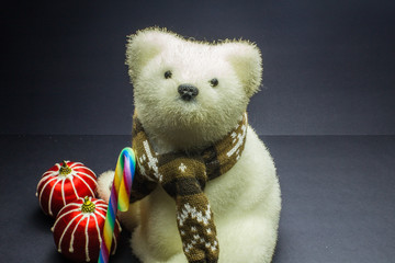 White polar bear toy with candy and two stripes Christmas balls on black background