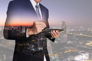 Double exposure of businessman working with tablet,  night cityscape as Communication concept