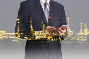 Double exposure of business man hand hold and oil refinery industry plant in the night as Energy and Technology concept.