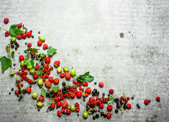 Berries with mint leaves on stone background.