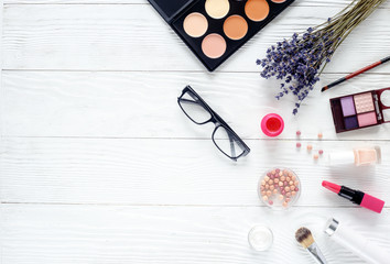 make up set on wooden table with lavender top view