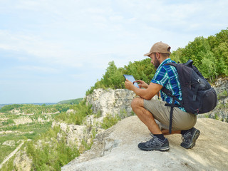 Man tourist uses tablet computer sitting on the edge of a cliff