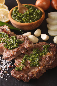 Argentine cuisine: grilled beef steak with chimichurri sauce macro. Vertical