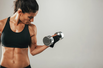 Strong female athlete lifting dumbbell