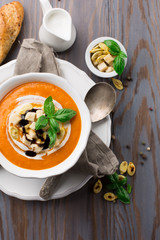 Homemade pumpkin soup with cream, croutons and basil on rustic wooden background, top view