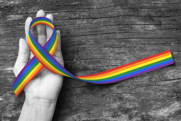 Rainbow color ribbon awareness on human hand on BNW background, clipping path: Symbolic color logo icon for equal rights in love and marriage social equality of LGBT community/ people concept
