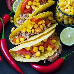 Mexican tacos cooked with chicken mince, tomatoes and yellow corn and served with chili pepper, lime and garlic