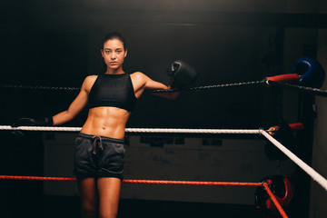 Portrait of young female boxer leaning on ropes