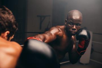 Handsome black boxer at strikes his opponent