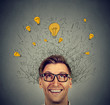 Excited man with many ideas light bulbs above head looking up