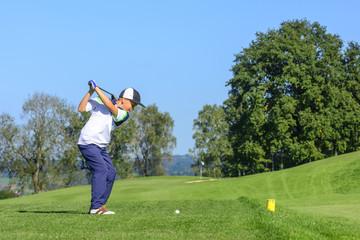 Jugendlicher Golfer beim Abschlag