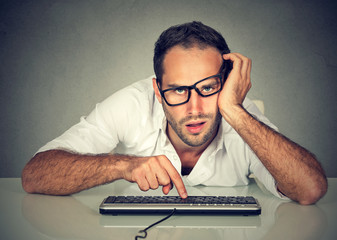 Sleepy worker young man working on computer