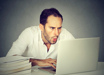 shocked business man sitting in front of computer looking at screen
