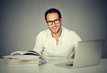 Man student using his notebook and reading books
