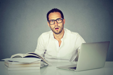 Surprised confused man studying at table with sbooks and laptop