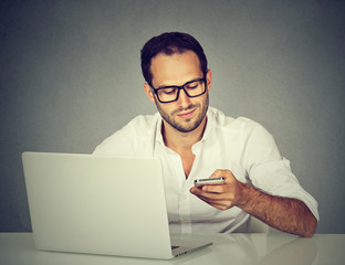 Young man with laptop texting on mobile phone sitting at table
