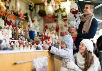 Happy family choosing Christmas decoration at Christmas market