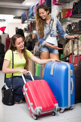 Girl buying suitcase in store