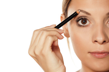 young beautiful woman shaping her eyebrows with a pencil for eyebrows