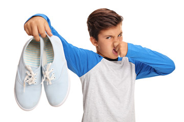 Boy holding a pair of smelly shoes