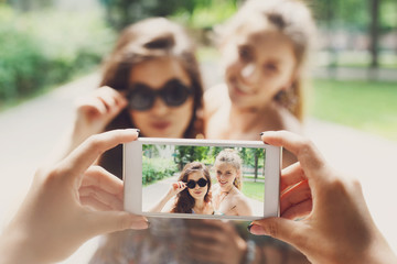 Girls friends taking photos with smartphone outdoors