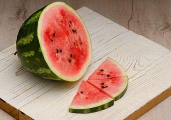 Half of cut in watermelon and three slices on white wooden board