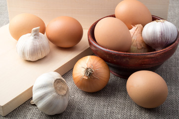 Raw eggs, onions and garlic on a background of burlap