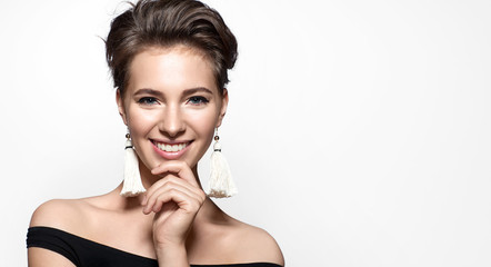 Beautiful woman with a charming smile in a black dress and earrings tassels