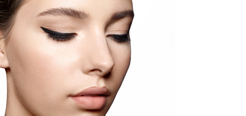 Woman with clean skin with natural make-up and with black arrows on the eyes close up