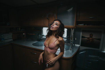 Sexy woman in underwear leans on table and smoking
