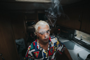 Man with bleached hair with face covered with smoke