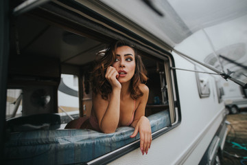Portrait of young woman in underwear looking at window