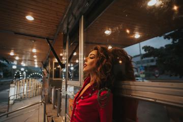 Pretty brunette woman in red coat lean on wall posing