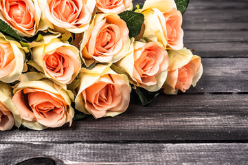 Pink roses on wooden background