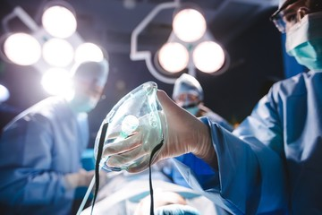 Surgeon holding oxygen mask in operation room