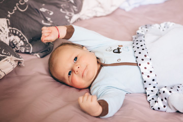 Portrait of cute adorable funny white Caucasian blond little baby boy newborn with blue grey eyes lying on large parents bed looking in camera, lifestyle candid, real life