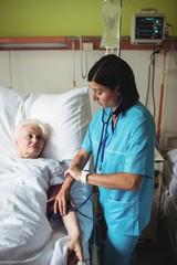 Nurse checking blood pressure of senior patient