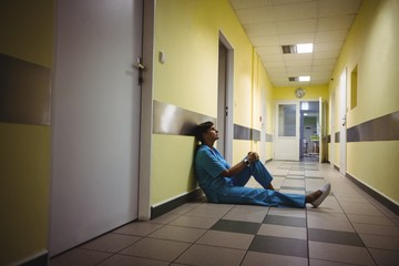 Depressed nurse sitting in corridor