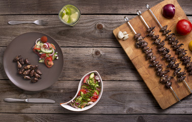 """Churrasco de curacao"",traditional Brazilian barbecue, grilled chicken hearts composition with tomatoes and onion salad an old wooden table."