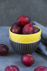 Plums in yellow bowl, separated, close up.Grey background and tablecloth.