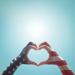 American flag pattern on people hands in heart shaped form against vintage sky background w/ clouds: Memorial day Happy columbus day Patriot day, USA Independence Labor Loyalty day symbolic concept.