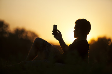 Silhouette of one man taking picture in the sunset outdoor.