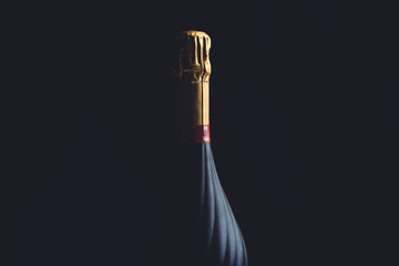 Champagne bottle on a black background with space for text