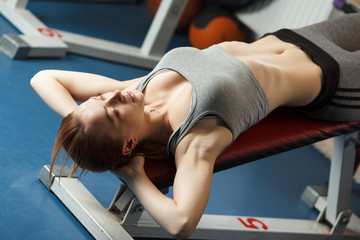 Young strong girl take breather in gym