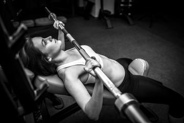 Women in Gym Lifting Bar