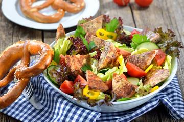 Bayerische Salatschüssel: Gebratene Milzwurst auf buntem Salat mit Breze serviert - Bavarian salad: Fried sausage with pieces of spleen served on a colorful salad