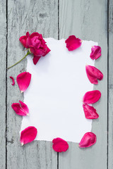 Love background with copy space for text. White paper on wooden table with red rose and petals Top view.