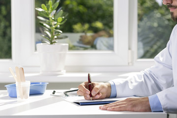 doctor sitting by the table and writing a document